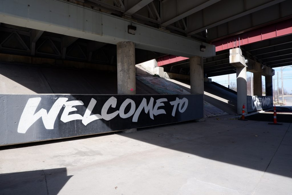 Welcome to Greenwood sign painted white under the bridge