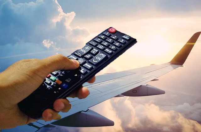 A Television remote with background of plane in the clouds